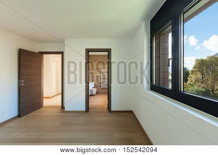 Interior of empty apartment, wide room with bathroom, wooden floor