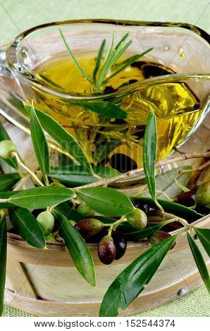 Raw Green and Black Olives with Leafs with Olive Oil in Glass Gravy in Wooden Bowl closeup on Green Textile background