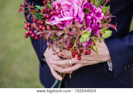 Close up view of groom holding bouquet of flowers