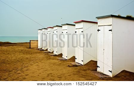 White Wooden Cabanas on Sand Beach in a Row on Blue Sky and Sea Edge Background Outdoors. French Atlantic Coast