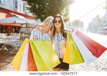 Two young women with shopping bags walking on the street together