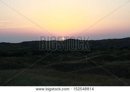 ondergaande zon achter de duinen van Texel