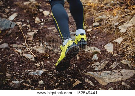 legs runner skyrunners man running uphill on track of dirt and stones