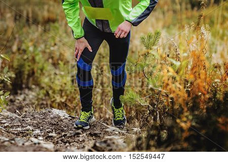 athlete runner skyrunners running uphill on autumn trail of mud and stones