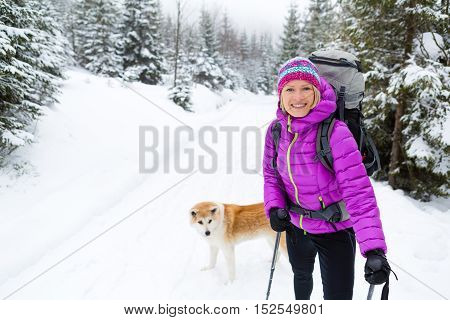 Woman hiking in white winter forest woods with akita dog. Recreation fitness and healthy lifestyle outdoors in snowy cold nature. Motivation and inspirational winter landscape.