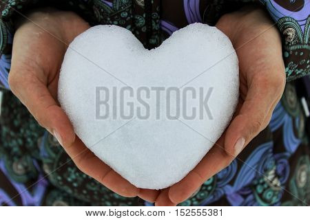 Snow on the palms of the hands in the form of heart