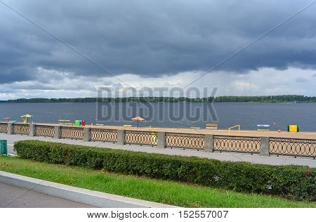 View on the Volga quay of the Samara city in anticipation of thunderstorm. City embankment, green hedgerow, beautiful sky with cumulus clouds before rain at cloudy autumn day