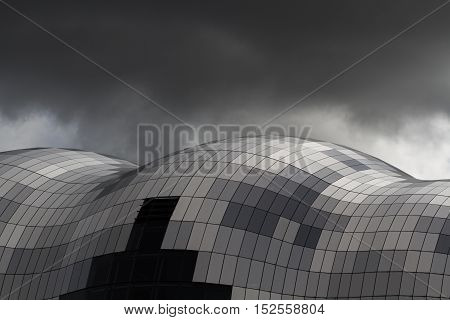 NEWCASTLE, UK - OCTOBER 17, 2016. The Sage glass building in Gateshead, Newcastle, UK is a popular music venue and music education building shown under a stormy sky with black clouds.