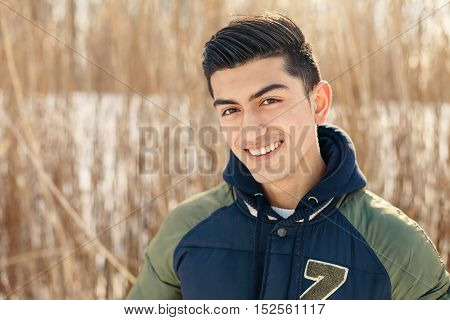 Good looking, confident millenial guy enjoying wintertime in a snow filled park