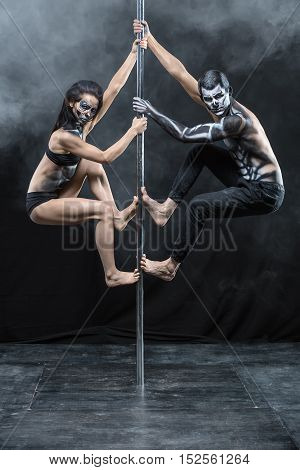 Photo of the couple of pole dancers with a horrific body-art in the dark studio with a cloud of a smoke. They are hanging on a pylon. Guy and the girl dressed in black sportswear. Vertical.