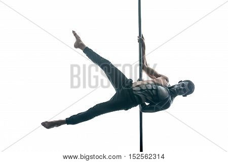 Athletic pole dancer with horrific body-art hangs horizontal on a pylon in the studio on the white background. He wears black pants and looks into the camera. His legs are outstretched to the sides.
