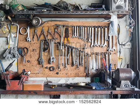 Old tools hanging on wall in workshop Tool shelf against a wall