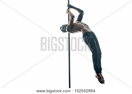 Attractive pole dancer with horrific body-art hangs on a pylon in the studio on the white background. He wears black pants. Guy holds the pylon with his hands and holds the legs together. Horizontal.