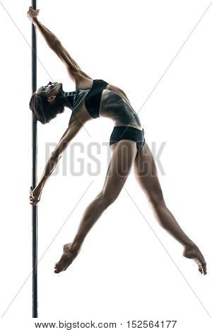 Slim pole dancer with a body-art hangs with stretched arms and legs on a pylon in a studio on a white background. She holds her hands on the pylon. Girl wears black sport underwear. Vertical.