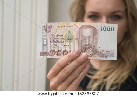 Closeup of 1000 Thai Baht note withdrawned from ATM over blurred woman's face