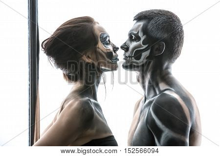 Photo of couple of pole dancers with horrific body-art which are preparing to a kiss in the studio on the white background. Girl wears black sportswear. Horizontal. Close-up.