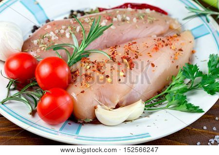 Raw chicken breast with spices ready for baking - delicious meal