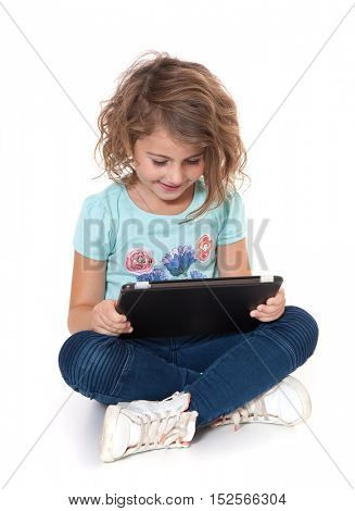 Little girl using tablet device. All on white background.