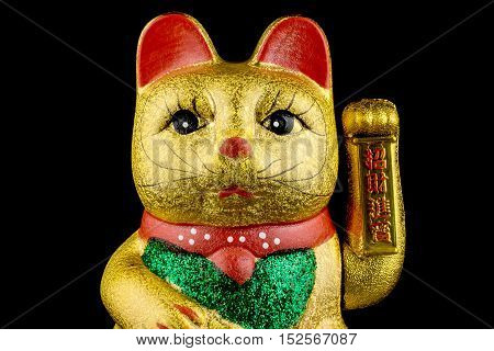 Beckoning Cat studio shot of golden asian figurine with black background