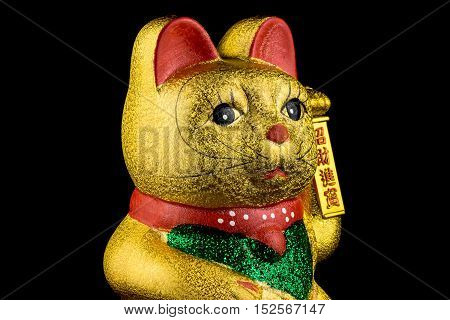 Beckoning Cat studio shot of golden asian figurine with black background