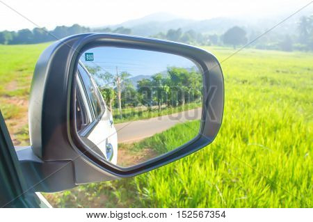 green field mountain and the wing mirror of the car