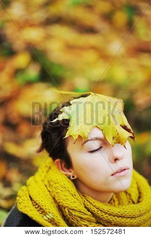 Portrait of a young pretty girl in a knitted scarf mustard color with a maple leaf on head in autumn Park close up.