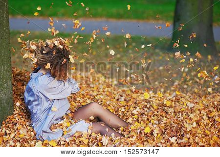 jovial young teenage girl throwing autumn leaves in the air sitting on the ground in a big pile of fallen leaves