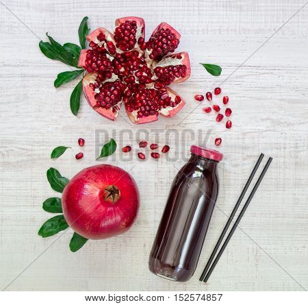 Left bottle of pomegranate juice near pomegranate, pomegranate slices, seeds on a light white wood background right empty space. Bottle of pomegranate juice and pomegranates. Horizontal. Top view.