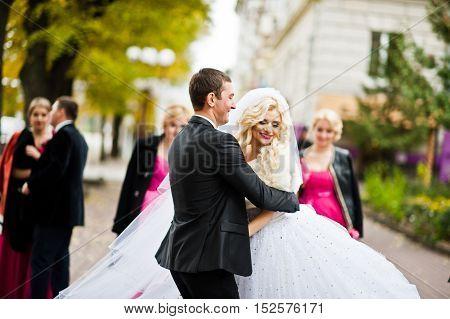 Newlyweds walking backgound bridesmaids and groomsman  at wedding