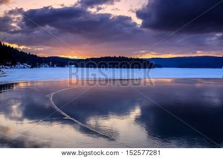 Winter landscape of ice cold lake in the mountain and dark clouds in the sky
