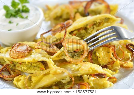 Fried Swabian ravioli, so-called Maultaschen, with vegetarian filling served with roasted onions, scrambled egg and creamy herb cheese