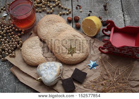 Christmas tea with cookies, Christmas toys and sweets, lemon, gold beads, dried herbs, welding