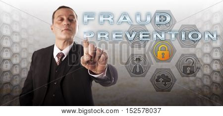Experienced manager with assertive facial expression is touching FRAUD PROTECTION on a control screen. Information technology concept for civil and criminal computer offense via deliberate deception.