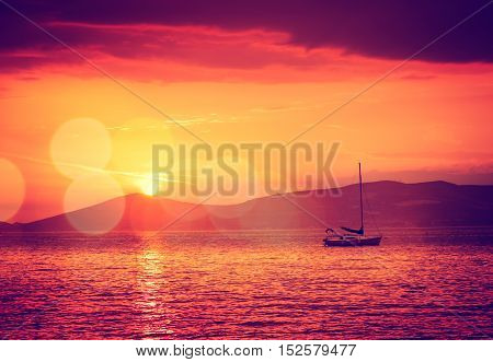 Beautiful Seascape with Sailing Yacht in Calm Bay at Sunset. Quiet Sea. Beautiful Bokeh. Toned and Filtered Photo with Copy Space.