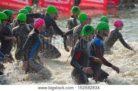 GRAFHAM, CAMBRIDGESHIRE, ENGLAND - MAY 22, 2016:  Triathlon swimmers entering open water swim stage.