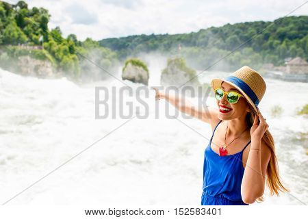 A portrait of a young female tourist near the famous Rhine waterfall. Woman having great vacation in Switzerland