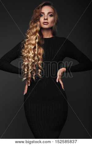 Studio portrait of a sexy long hair blonde in black dress