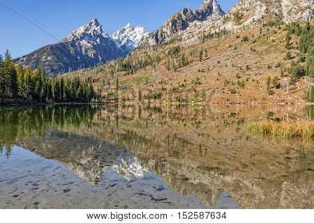 the Tetons in fall reflected in String lake in Teton National Park