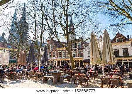 Delft, Netherlands - April 8, 2016: Colorful street view, people in traditional dutch restaurant in the center Delft, Holland