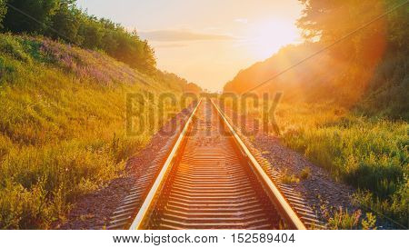 The Scenic Panorama Landscape With Railway Going Straight Ahead Through Summer Hilly Meadow To Sunset Or Sunrise In Sunlight. Lense Flare Effect.