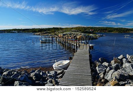 Wooden pier with small, moored ships between bare rocks on the seaside of Donsö, an island of the archipelago of Gothenburg (Göteborgs skärgård), Sweden