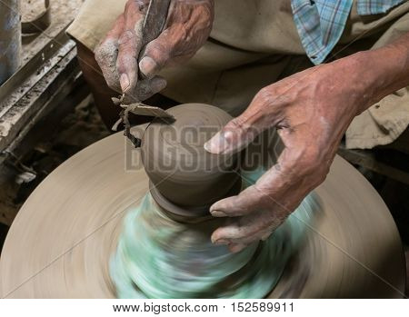 Hands working with clay on pottery wheel.