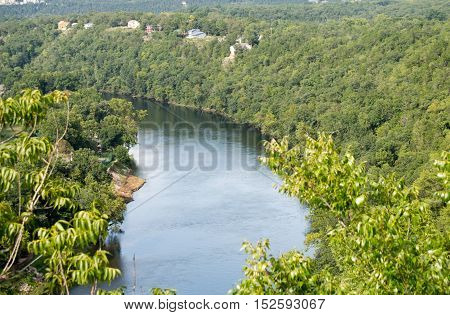 Clear river with green trees on banks, winding