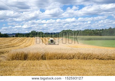 Harvesting of a grain field with an approaching combine harvester