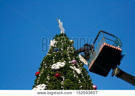 Volgograd Russia - December 20 2008: A worker decorates a Christmas tree