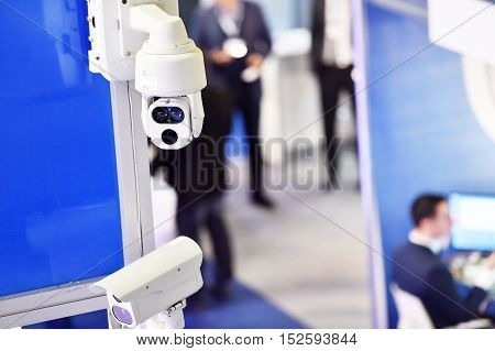 Surveillance camera inside a company with people in the background