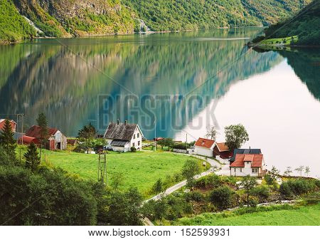 Top View Of Scandinavian Houses In Norwegian Village On Shore Of The Narrowest Fjord In Norway - Naeroyfjord. Beautiful Fjord At Summer Season.