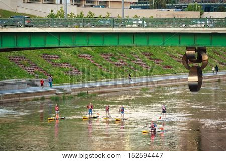 Vilnius, Lithuania - July 08, 2016: Group Of Young People Stand Up Paddling SUP On Neris River Under Green Bridge With Three Hanging Metal Rings.