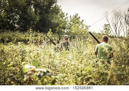 Hunters breaking through bushes during hunting season in summer day