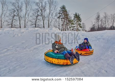 Happy children enjoying a winter sleigh ride on a winter slope